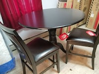 round black wooden table with four chairs