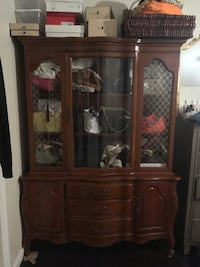 Antique solid wood china cabinet. Beautiful display. Has some minor scratches. Very heavy needs to be picked up with help. Breaks into 2 pieces for easy moving! 219 mi