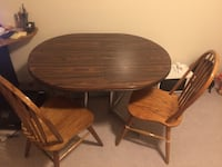 round brown wooden table with four chairs dining set Kelowna, V1W 3Z3