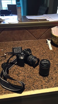 black Olympus DSLR camera with lens