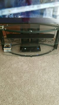 Black metal and glass TV stand holds 55' TV