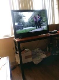 black flat screen TV with brown wooden TV stand Hyattsville, 20782