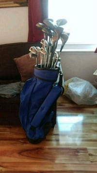 blue and black golf bag with golf clubs
