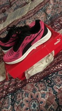 pair of pink-and-black Puma shoes on box