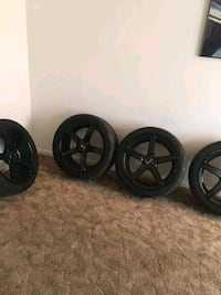 four black 5-spoke car wheels with tires