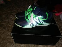 pair of green-and-black Adidas shoes with box
