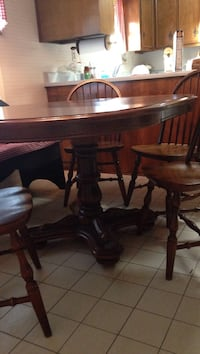 oval brown wooden pedestal table with four windsor chairs