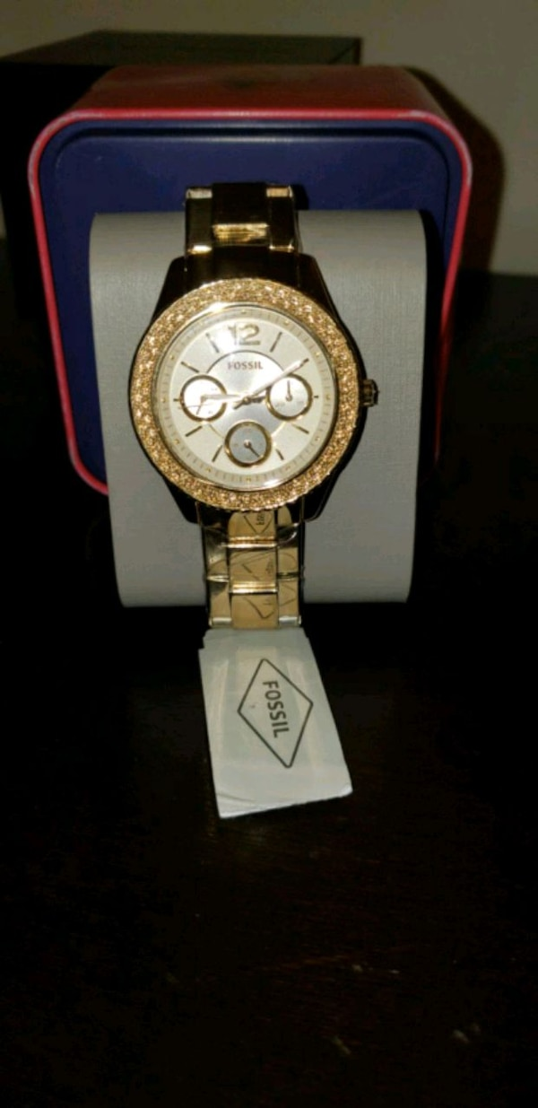 round silver chronograph watch with gold link bracelet