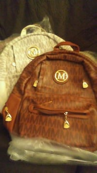 two monogrammed white-and-brown Michael Kors leather backpack