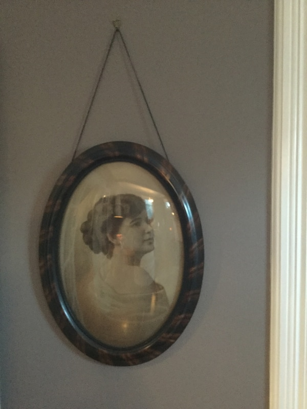 Black hair woman painting in oval frame.