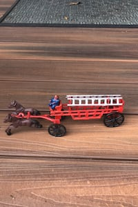 Vintage cast iron horse drawn fire wagon with ladders.