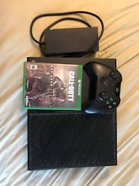 black Xbox One console with controller and game case