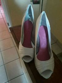 pair of women's white leather peep-toe pumps