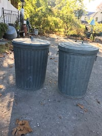 2 metal trash cans with lids