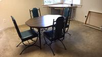 round brown wooden table with four chairs dining set National City, 91950