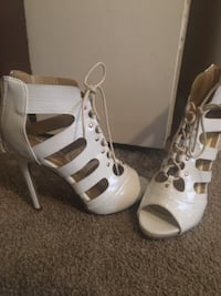 pair of women's white patent leather open-toe high-heeled zip-back booties