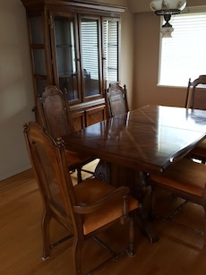 rectangular brown wooden table with four chairs and china cabinet
