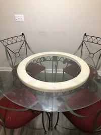 Round clear glass-top table with gray steel base 525 mi