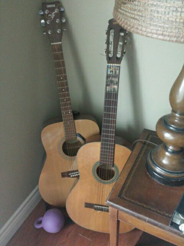two natural finish classical and acoustic guitars