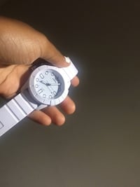 round silver-colored analog watch with white strap