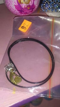 gold-colored hand holding heart pendant with black string necklace and resealable pack Halifax, B3L 3X8