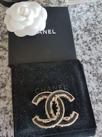 gold-colored and black Chanel accessory with box