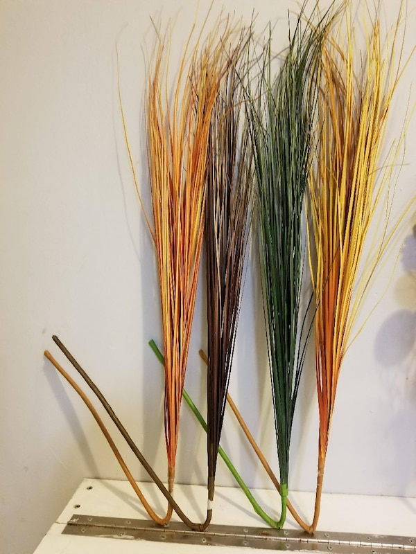 two yellow, brown, and green broom stick decors