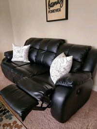 Tufted black synthetic leather couch with recliners and loveseat