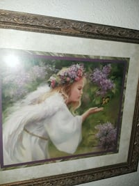 angel wearing wreath painting with brown frame