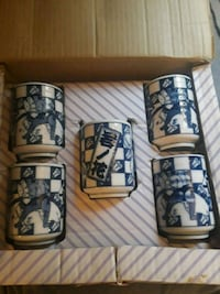 five white-and-blue ceramic mugs with box