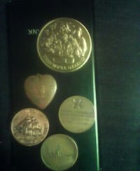 five gold-colored coins and heart pendant