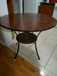 round brown wooden table with black metal base Markham