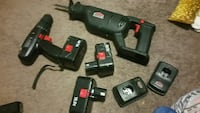 black reciprocating saw and cordless hand drill with battery packs