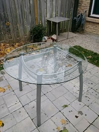 round clear glass-top table with gray steel base Cambridge, N1R 6Z5