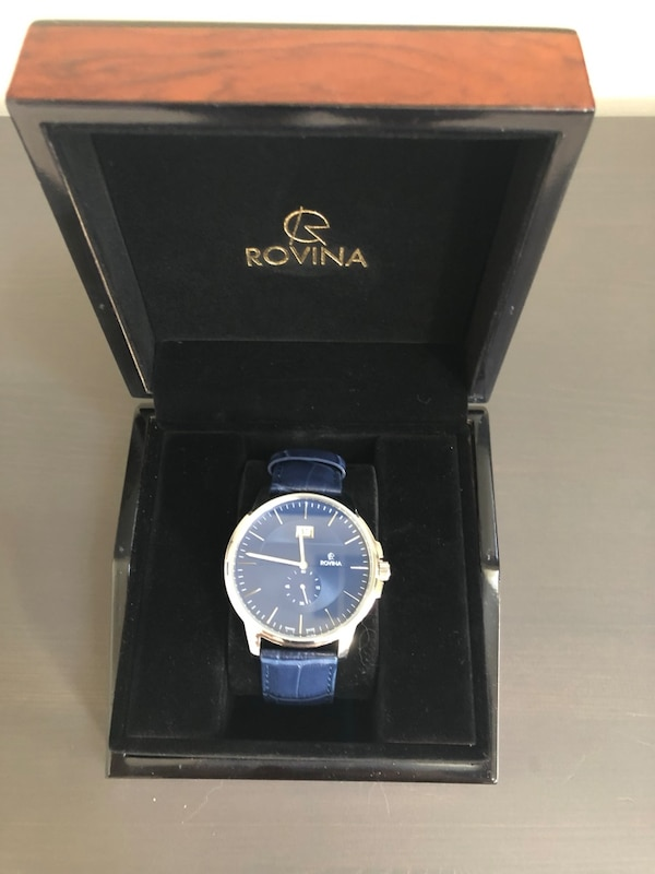 Round silver analog watch with blue leather strap in box
