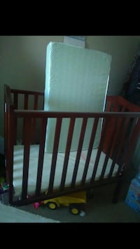 baby's brown wooden crib with white mattress