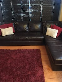 Dark brown leather sectional, pillows, dark brown tv stand , 2 floor lamps, additional burgundy and white rug included null