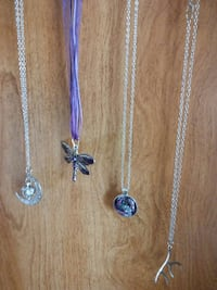 four silver-colored pendant necklaces