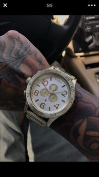 round silver Nixon chronograph watch with link bracelet