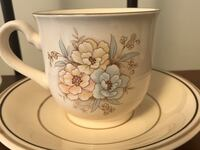 Two place setting of footed cup and saucer
