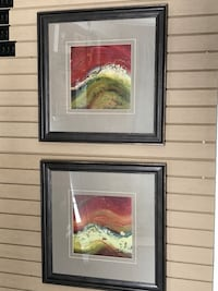 two black wooden framed painting of red-and-brown waves