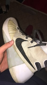 unpaired of beige and white Nike basketball shoe