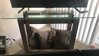 rectangular glass-top TV stand with brown wooden base
