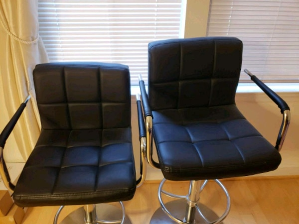 two black leather padded rolling chairs