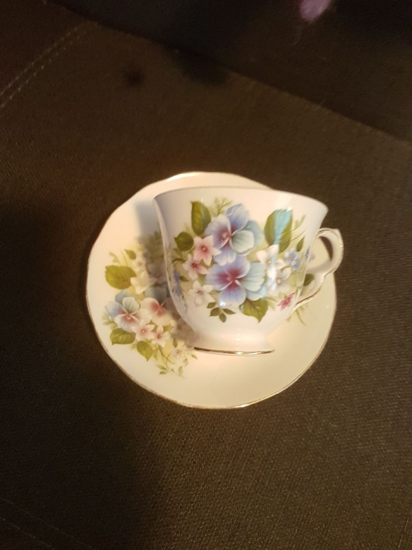 white-blue-and-green floral ceramic teacup and saucer