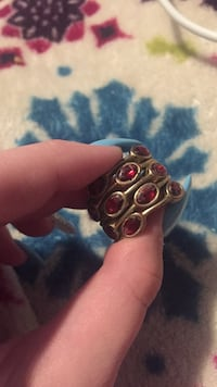 Gold-colored red gemstone encrusted ring