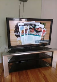 black flat screen TV with brown wooden TV stand Montréal, H1H 5B1