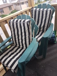 two gray adirondack chairs with black and white striped cushions