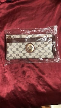brown and black monogrammed Coach leather wristlet