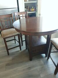 round brown wooden table with four chairs dining set Calgary, T3M 1M7